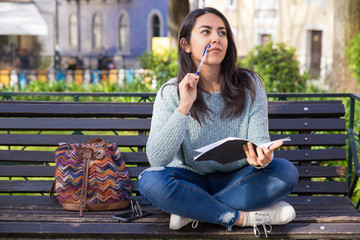 Thoughtful woman making notes and sitting on bench outdoors