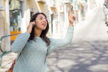 Young woman talking on phone and hailing for taxi
