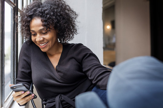 Smiling businesswoman using cell phone in office