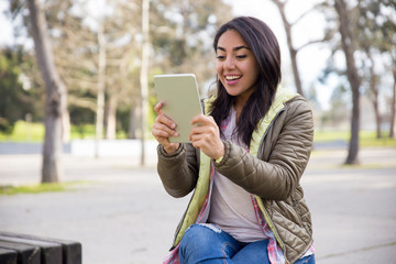 Cheerful young woman talking via video link on tablet