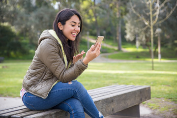 Excited young woman chatting online in park