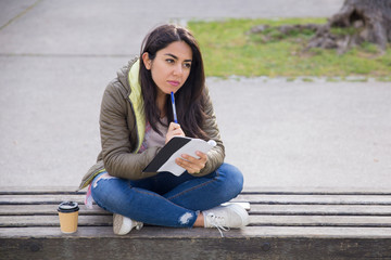 Pensive young woman in jacket making notes in park