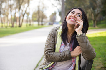 Cheerful excited girl talking on mobile phone