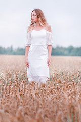 Bride in a white dress posing on a background of wheat