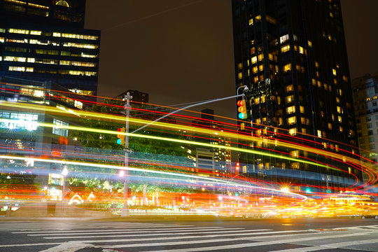 Light trails on city street by illuminated buildings