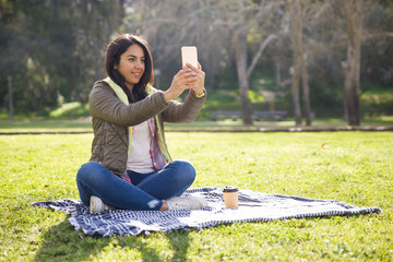 Excited student girl resting in park and taking selfies