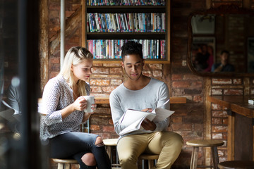 Man showing papers to woman while sitting at cafe
