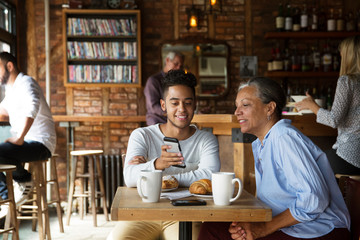Smiling man showing phone to woman while customers relaxing at cafe