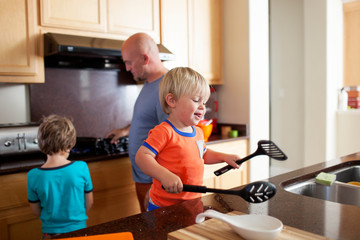 Father teaching son while boy playing with spatulas in kitchen at home