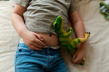 Midsection of boy with toy sleeping on bed at home