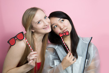 Two young women. One blonde and Slavic appearance, the other brunette, Asian appearance. They're happy to be together. Portrait of two girlfriends.