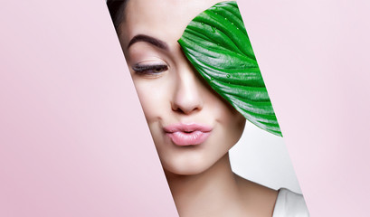 Portrait of young beautiful woman with healthy glow perfect smooth skin holds green tropical leaf,...