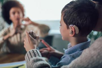 Smiling deaf boy learning sign language. Selective focus. Fototapete