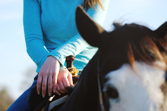 Woman with hands on saddle close up with horse.  Western concept of horseback riding.