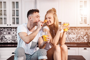 Man feeding his wife croissant while she smiling to him and holding glass