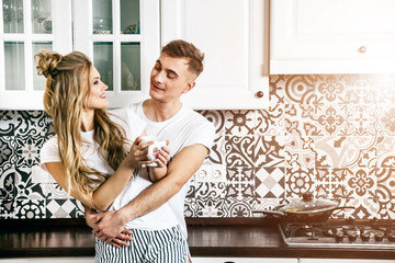 Blonde young woman and handsome blonde man enjoying spending time together while standing on light modern kitchen