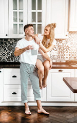 Happy blonde couple embracing in kitchen in the morning