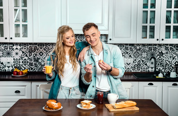 Couple in love having breakfast together in the kitchen