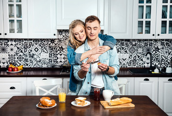 Young happy couple standing near the table in modern apartment and having breakfast together