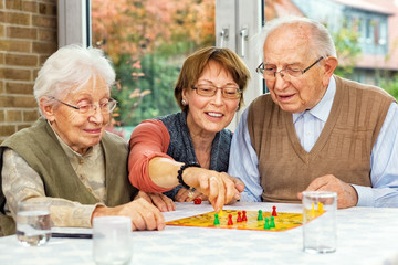 Elderly couple and daughter playing board game
