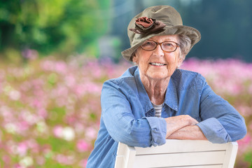 Happy mature woman with casual wear and a hat in front of a pink cosmos flower field