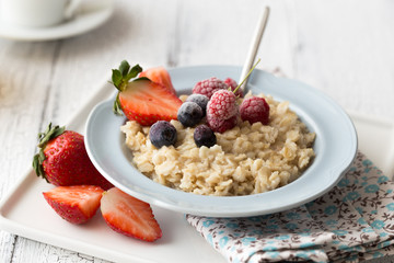 Breakfast oatmeal porridge with fruits berries and coffee cup. Oatmeal with strawberries and banana. Healthy breakfast concept.