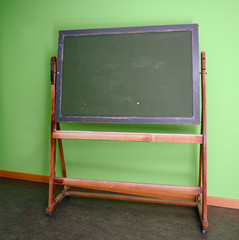 old school blackboard or chalkboard to use chalk to write on against a green wall, copy space