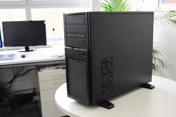 black server computer in a tower case on a white table in the office, selected focus