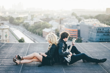 Couple in rock-n-roll style siting on the rooftop at the sunset sky background. Girls hair flapping on the wind , man playing on guitar.