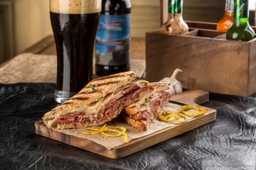 grilled Reuben Sandwich with dark beer on wooden cutting board