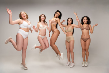 five attractive multicultural young women in lingerie having fun and jumping, body positivity concept