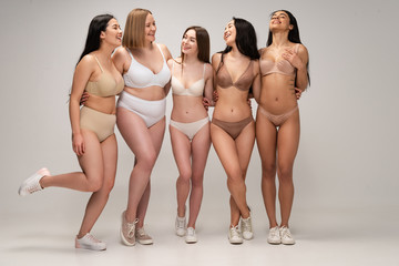 five cheerful multicultural young women in lingerie hugging while posing at camera, body positivity concept