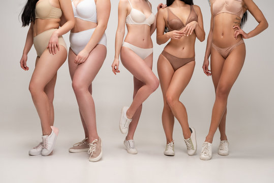 cropped view of five multicultural women in underwear and sneakers posing at camera, body positivity concept