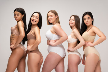 five pretty multiethnic girls in lingerie posing at camera with hands on hips isolated on grey, body positivity concept