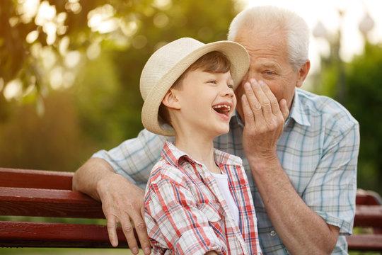 Senior man whispering to his grandson