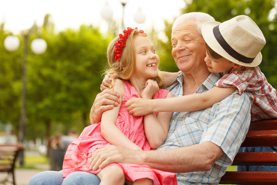 Happy senior man relaxing outdoors with his grandkids