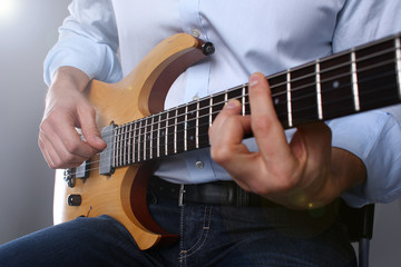 Male arms holding and playing classic shape wooden electric guitar closeup. Six stringed learning musical school education art leisure electrical vintage stage shop having fun enjoying hobby concept