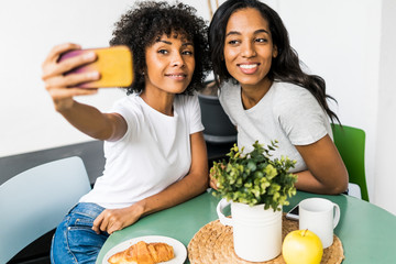 Two happy girlfriends sitting at table taking a selfie