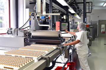 Arbeiterin am Fliessband in der Lebensmittelindustrie - Produktion von Pralinen in einem Werk // Worker on an assembly line in the food industry - Production of pralines in a factory