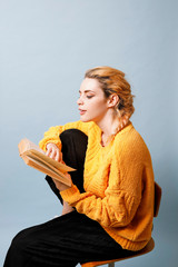 Young woman wearing yellow knit pullover in front of blue background reading a book