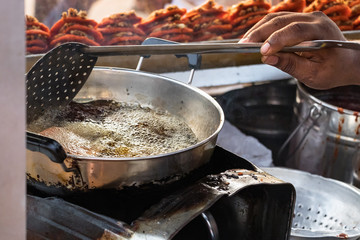 Male hand of a cook frying crabs on a  pan outdoors in a street market in Colombo, Sri Lanka