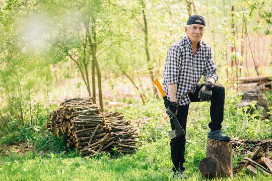 Senior man with axe chopping wood. Elderly arborist man working in garden. Active retirement lifestyle concept.