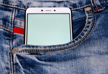 White smartphone in a white screen jeans pocket