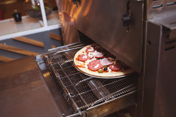 Fresh cooked pizza modern industrial oven in a restaurant