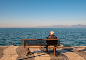 A senior man sitting on a bench on the shore of Lake Garda in a sunny spring day, Lazise, Veneto, Italy