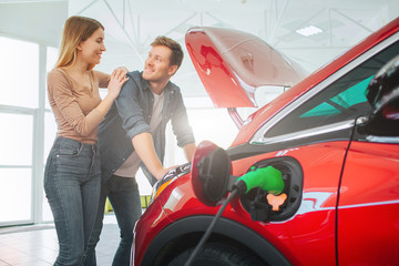 Young smiling family buying first electric car in the showroom. Attractive couple are enjoy to buy an eco-friendly car. Electric car sale concept