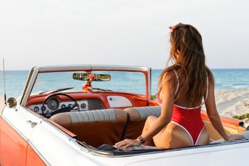 Sexy woman wearing  red swimsuit  is sitting inside a retro cabriolet car
