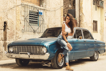 Woman is posing beside old car