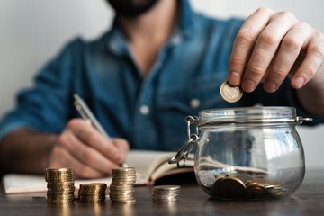 business accounting with saving money with hand putting coins in jug glass concept financial.