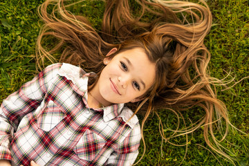 Portrait of smiling girl with long hair lying on a meadow